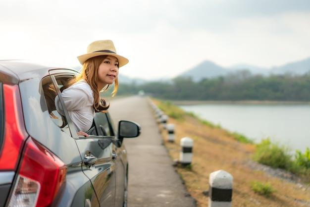 Vrouw toerist op zoek uitzicht buiten het raam tijdens het rijden op road trip reizen vakantie.