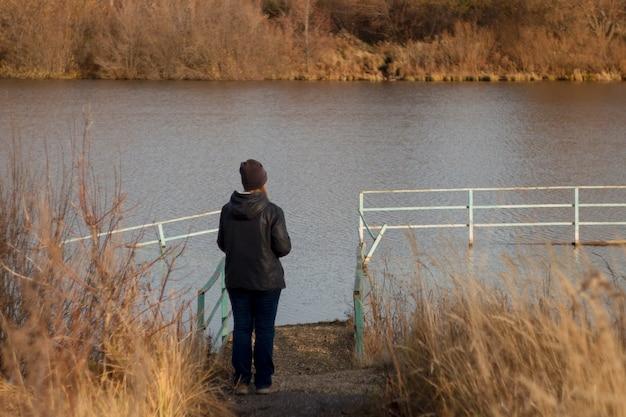 Vrouw toerist staat op de pier op de vijver in het najaar park