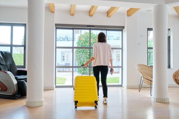 Vrouw toeristische gast met koffer in de lobby van het hotel, achteraanzicht. reizen, vakantie, toerisme, vrije tijd, weekendmensen