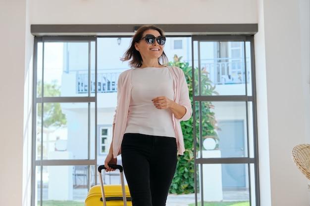 Vrouw toeristische gast met koffer in de lobby van het hotel. reizen, vakantie, toerisme, vrije tijd, weekendmensen