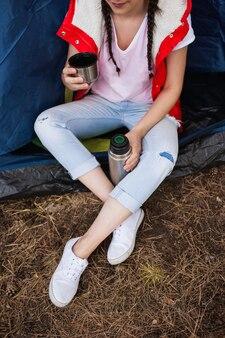 Vrouw toeristische levensstijl ontspanning tent concept. verwarmen met thee. toeristische momenten.