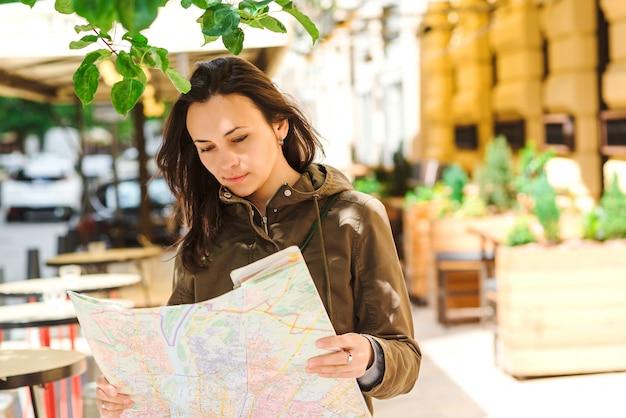 Vrouw toeristische locatie kaart in handen houden bij stad straat.