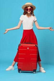 Vrouw toeristische rode koffer vakantie plezier zonnebril reizen