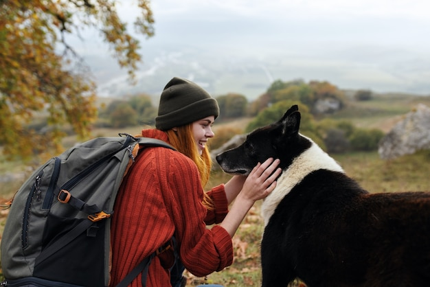 Vrouw toeristische rugzak spelen met hond reizen vriendschap