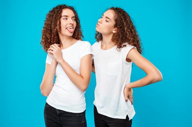 Vrouw tong haar zus tweeling tonen over blauwe muur
