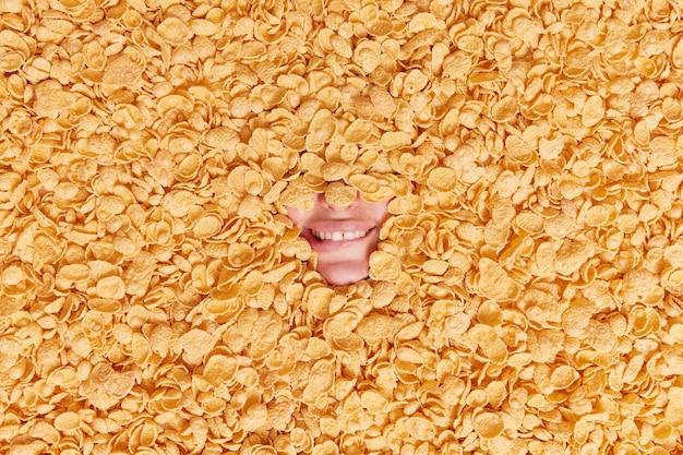 Vrouw toont alleen mond bijt lippen toont witte tanden gaat heerlijk ontbijten omringd door droge granen houdt zich aan gezonde voeding verdronken in cornflakes.