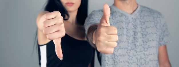 Vrouw toont duim naar beneden, man toont duim omhoog