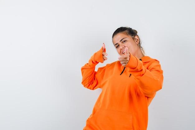 Vrouw toont geweergebaar in oranje hoodie en ziet er gelukkig uit