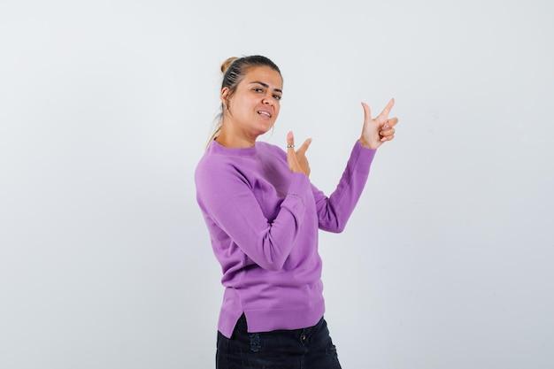 Vrouw toont geweergebaar in wollen blouse en ziet er zelfverzekerd uit