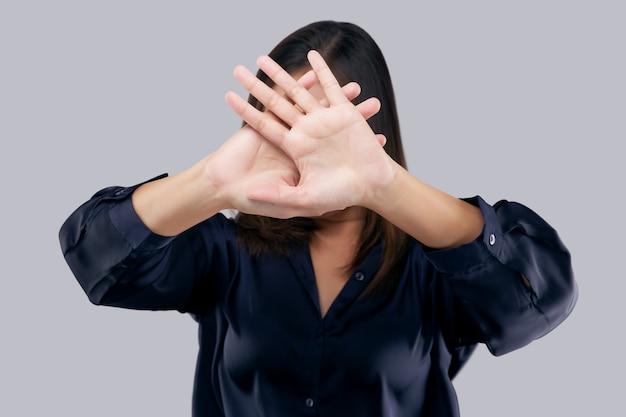 Vrouw toont haar ontkenning met nee op haar hand tegen een grijze achtergrond