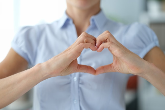 Vrouw toont hart handgebaar van liefde vrouw vrijwilliger toont sympathie en zorgconcept