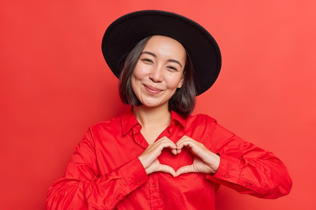 Vrouw toont hartteken in de buurt van borst ik hou van je gebaar draagt zwarte hoed en shirt poseert op levendig rood