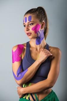 Vrouw toont kinesiotapes die op haar lichaam zijn geplakt.
