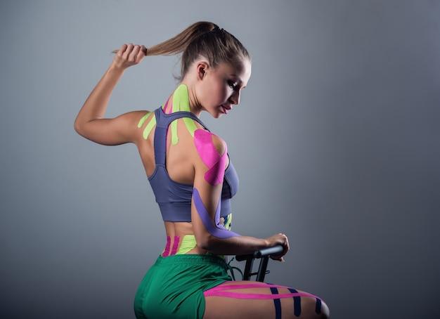 Vrouw toont kinesiotapes die op haar lichaam zijn geplakt