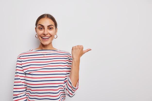 Vrouw toont kopieerruimte demonstreert promotiepunten duim weg, gekleed in casual gestreepte trui op wit