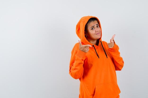 Vrouw toont pistoolgebaar in oranje hoodie en ziet er zelfverzekerd uit