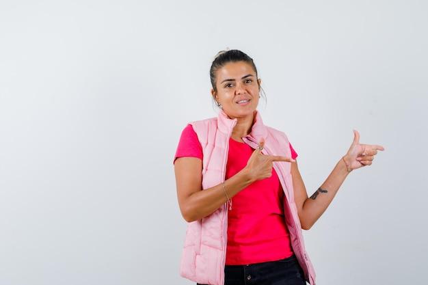Vrouw toont pistoolgebaar in t-shirt, vest en ziet er zelfverzekerd uit