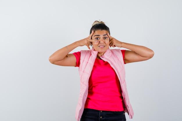 Vrouw toont v-teken bij oog in t-shirt, vest en kijkt opgewonden