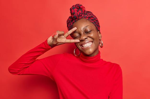 Vrouw toont v-teken dichtbij gezicht vredesgebaar houdt ogen gesloten glimlacht breed gekleed nonchalant poseert op felrode studio