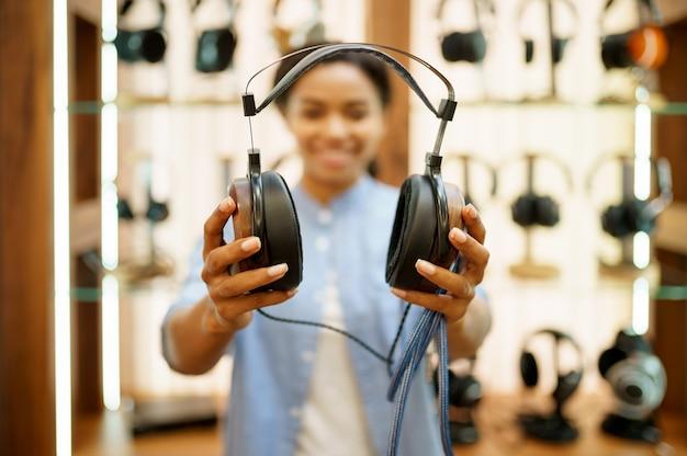 Vrouw toont vintage koptelefoon in de winkel van audiocomponenten. vrouwelijke persoon in muziekwinkel, showcase met oortelefoons, koper in multimediawinkel