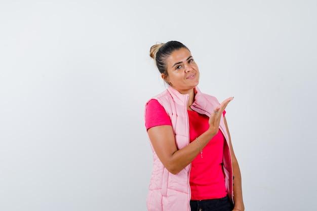 Vrouw toont welkomstgebaar in t-shirt, vest en ziet er zelfverzekerd uit