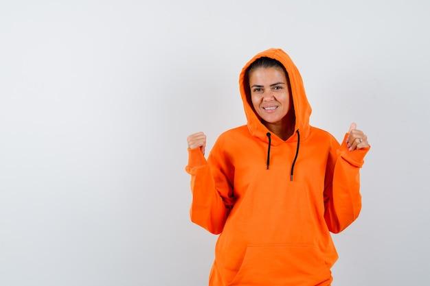 Vrouw toont winnaargebaar in oranje hoodie en ziet er gelukkig uit