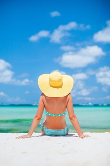 Vrouw tot op het strand genieten van zomervakantie kijken naar de zee