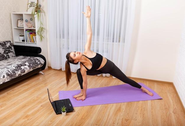 Vrouw trainen in de woonkamer vrouw beoefenen van yoga thuis