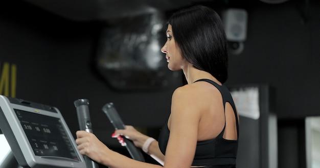 Vrouw trainen met elliptische loopmachine op sportschool. fitness meisje opleiding bij lopende machine. vrouw die op gymnastiekmachine loopt.