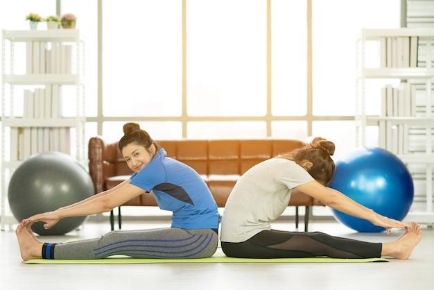 Vrouw trainen met fitness bal van sportvrouwen beoefenen van yoga. strekken met behulp van fitnessbal thuis