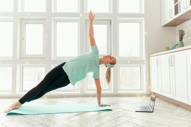 Vrouw trainen op de mat en kijken naar video op laptop