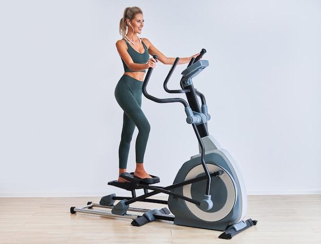 Vrouw trainen op x-trainer in fitnessstudio