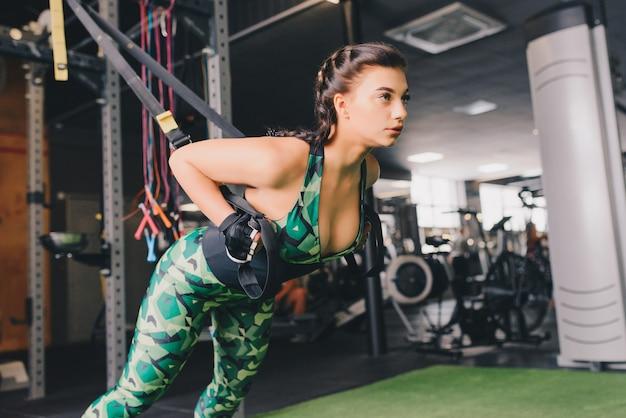 Vrouw training armen met trx fitness riemen in de sportschool doet push-ups trainen bovenlichaam borst schouders pecs triceps.