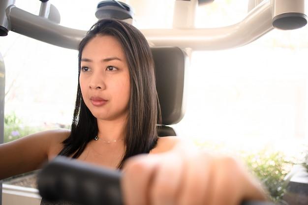 Vrouw training bankdrukken kabelmachine in de fitness gym.
