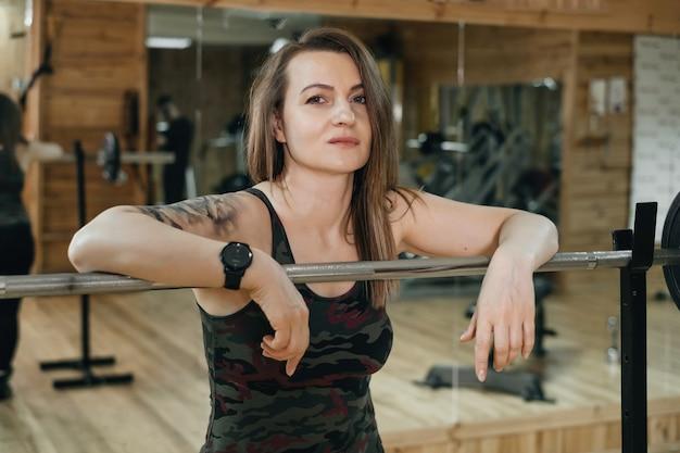 Vrouw training in sportschool, barbell press doen. gewichtheffen. mooie middelbare leeftijd vrouw powerlifter met tatoeage. sterk en fit lichaam, gezond levensstijlconcept. vrouw bij 40