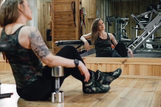 Vrouw training in sportschool, dumbbell press doen. gewichtheffen. mooie middelbare leeftijd vrouw powerlifter met tatoeage. sterk en fit lichaam, gezond levensstijlconcept. vrouw bij 40