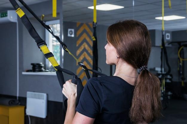 Vrouw training met trx in de sportschool, fitnesstraining met bandjes lus apparatuur.