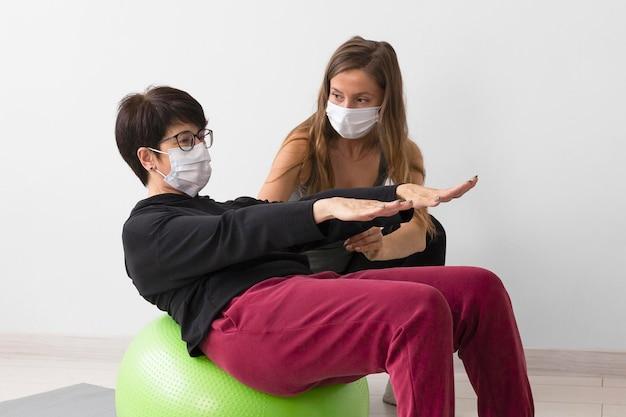 Vrouw training op fitness bal terwijl het dragen van een medisch masker