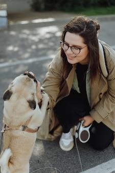 Vrouw traint de hond voor een wandeling op straat. honden voeren