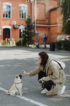 Vrouw traint de hond voor een wandeling op straat
