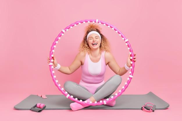 Vrouw traint met hoelahoep heeft een goede gezondheid mooie lichaamsvorm heeft fitnesstraining op mat oefeningen leidt regelmatig een sportieve levensstijl