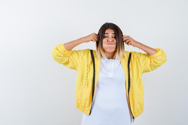 Vrouw trekt aan haar oren, waait wangen in t-shirt, jasje en kijkt geamuseerd, vooraanzicht.