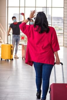 Vrouw trekt bagage en zwaait met haar vrienden met gezichtsmasker op de vertrekterminal van de luchthaven. meisje zegt hallo of hallo als ze metgezel ziet. reis met new normal om covid19 te voorkomen.