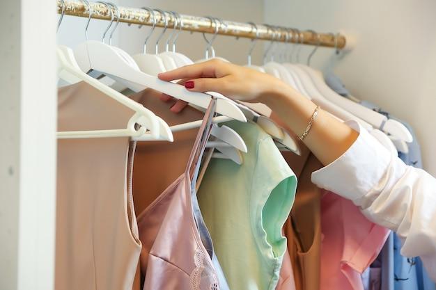 Vrouw trekt een hanger met kleren uit de kast
