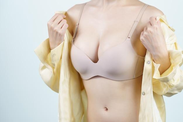 Vrouw trekt haar lichtgele shirt uit, ze is in lichte nude lingerie. borst implantaat chirurgie concept.