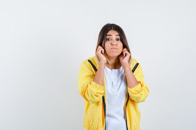 Vrouw trekt haar oorlellen in t-shirt, jasje naar beneden en kijkt voorzichtig, vooraanzicht.