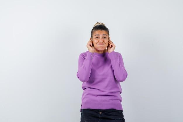 Vrouw trekt haar oorlellen naar beneden in wollen blouse en ziet er grappig uit