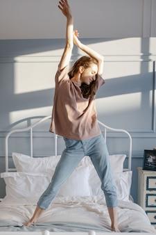 Vrouw trekt handen omhoog en staat in bed