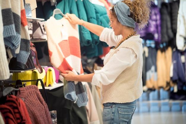 Vrouw trendy mode-levensstijl in een winkel die kiest wat ze gaat kopen, ze zoekt iets of wat kleding die ze leuk vindt - besteed geldconcept voor stedelijke stad volwassen levensstijl