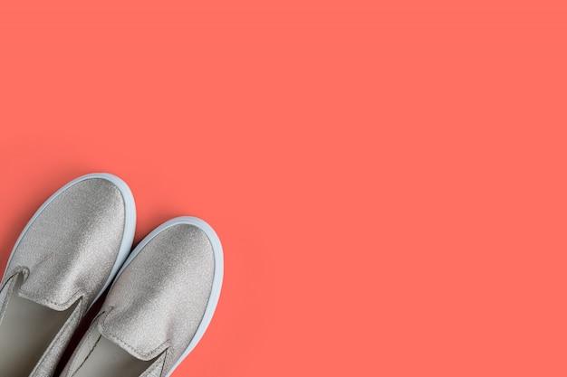 Vrouw trendy schoenen met glitter op koraal pantone van het jaar achtergrond met lege ruimte voor tekst